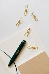 Pen, clips and notebooks on a white desk