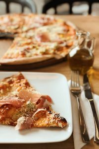 Kaboompics - Pizza with Prosciutto on the white plate