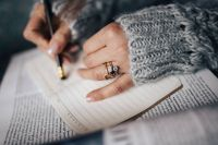 Woman in a grey sweater taking notes in an organizer