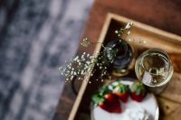 Kaboompics - Strawberries with cream and glass of white wine on wooden tray