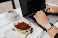 Kaboompics - A man with an elegant watch is working on a laptop. Classic tiramisu in a glass.