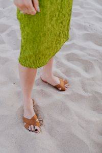 Kaboompics - A woman in a green dress and leather shoes on sand