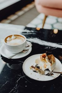 Kaboompics - Coffee and cake with meringue and whipped cream on black marble