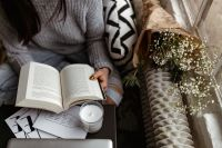 A woman in a sweater reads a book