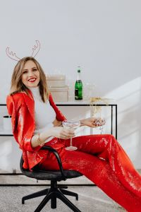 Kaboompics - Woman is sitting in red pants and a white shirt is sitting on a chair with champagne